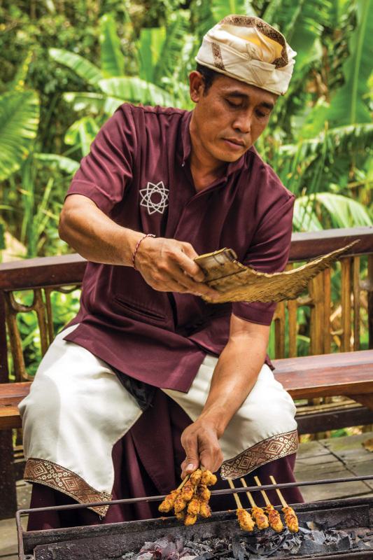 A man cooking satays