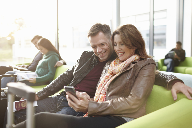Couple sits in airport looking at mobile phone together