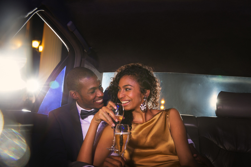 Glamorous couple in limo drinking chmapagne