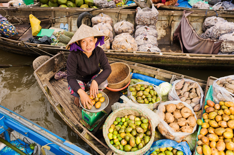 A vendor sells fruit from her boat at a Vietnamese floating market