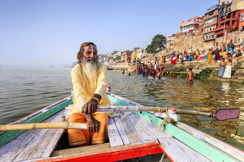 Old man rows along Ganges River