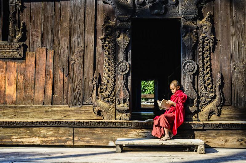 Monk sits on ornate temple steps in Myanmar