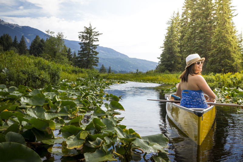 Woman looks back from canoe on River of Golden Dreams in Whistler