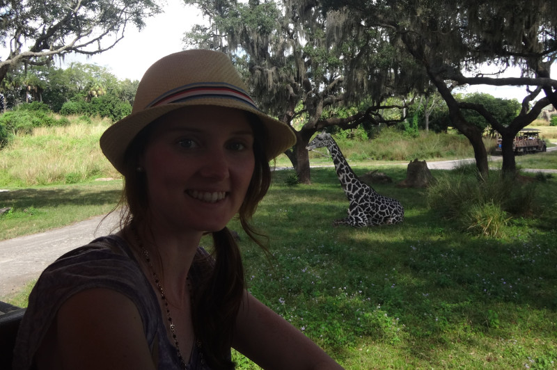 Photo of female tourist with giraffe in background