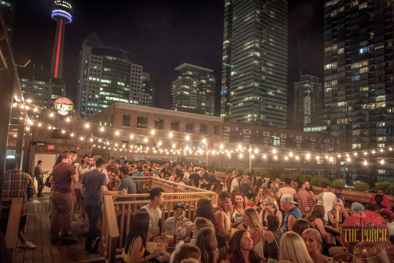 Young people party on a deck with city views of Toronto