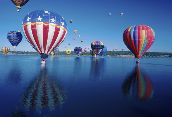 """Marvel at the """"mass ascension"""" where countless numbers of the massive balloons lift off at the Balloon Fiesta in New Mexico."""