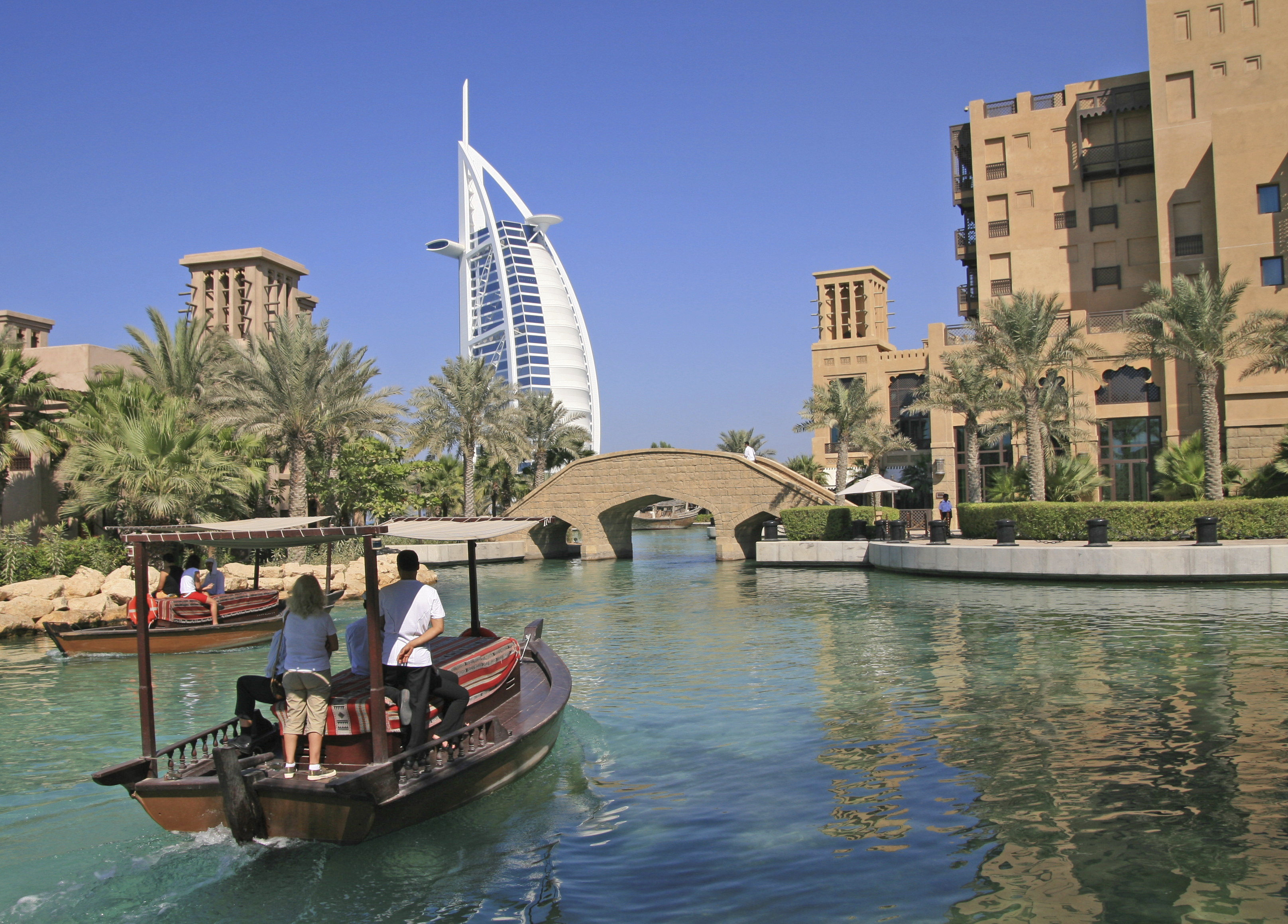 """This image: A view of the waterways at the Madinat Jumeirah in Dubai, with the Burj Al Arab in the background. Water taxis, or """"abras"""" will transport you to your hotel room and restaurants along the water"""