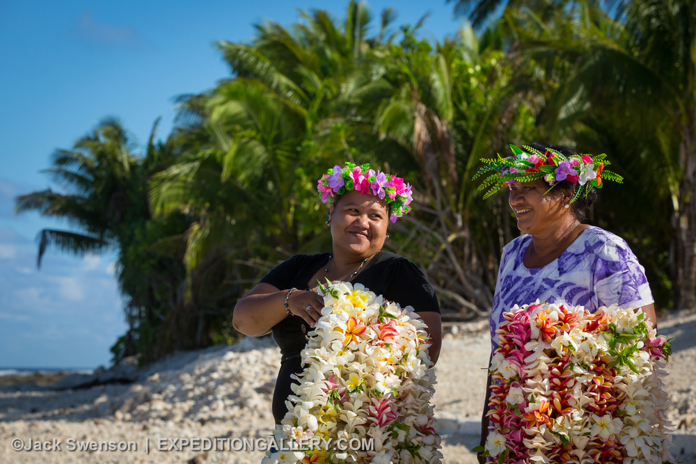 This image: Local women with arms full of flower leis to welcome visitors to Manihiki Atoll in the northern Cook Islands.
