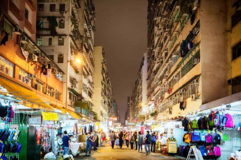 Temple Street night market with its bright lights under a canopy of apartment buildings. Image: Getty images.