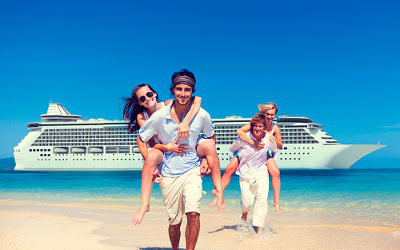 Couples piggy back on beach in front of cruise ship