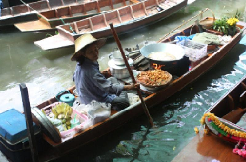 A vendor sells food from her boat in Thonburi, Bangkok