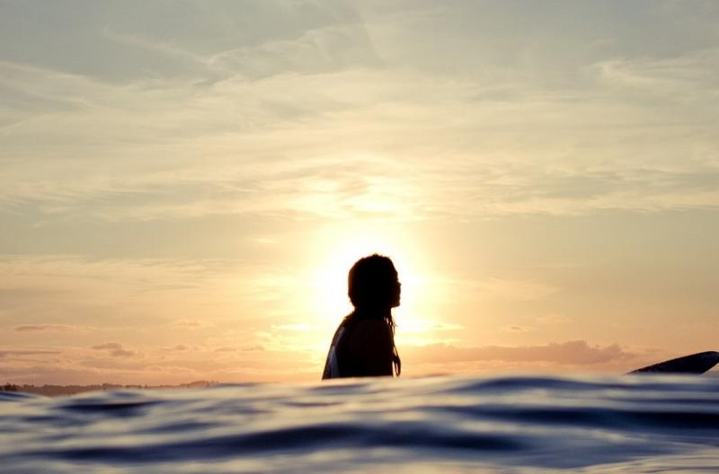 Silhouetted woman on longboard.