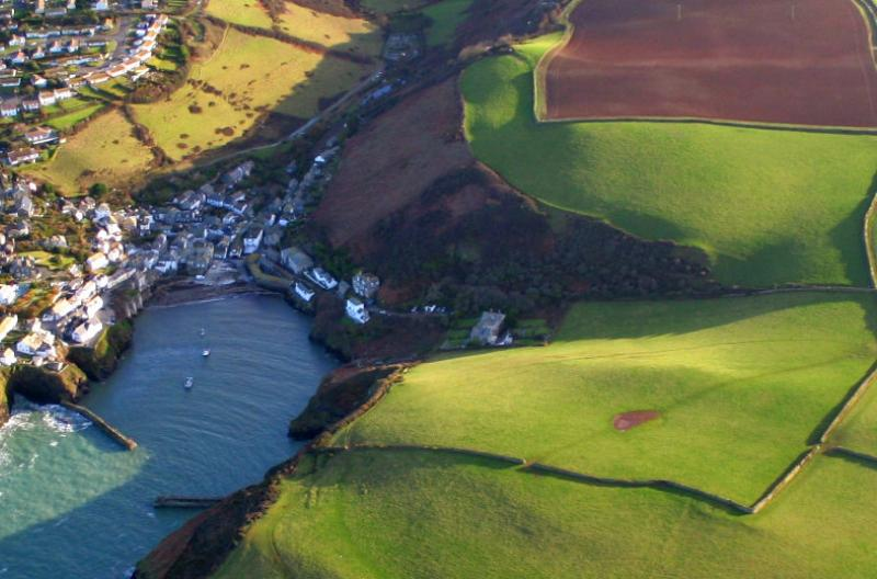 Aerial view of Cornish seaside town among green patchwork fields
