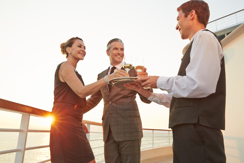 Couple is served drinks by a waiter on board luxury Seabourn cruise vessel