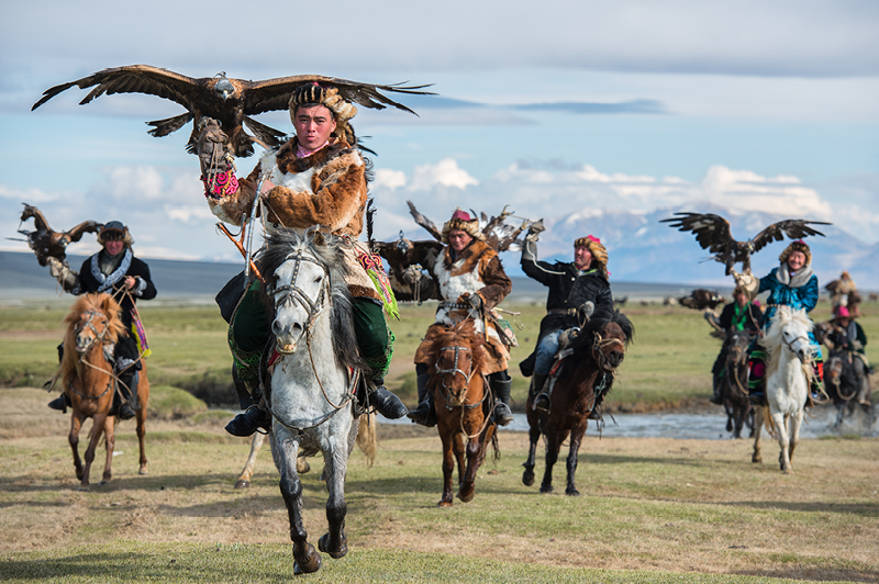 Kazakh Mongolian Cavalry Golden Eagle Hunter across the river in Altai Mountains