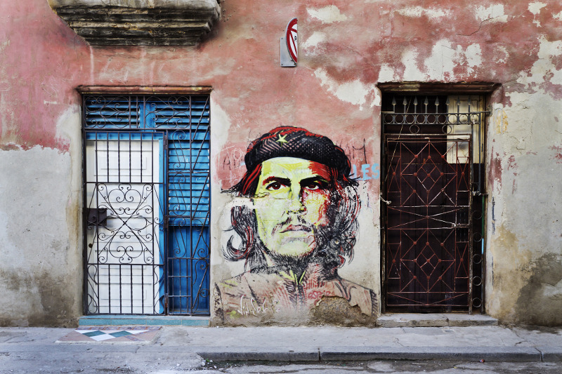 Mural of Che Guevara on adobe wall with Cuban flag