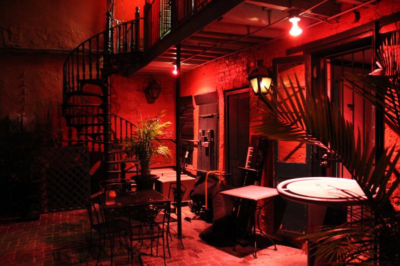 Cuban tango club red lights, palm tree in pot, empty