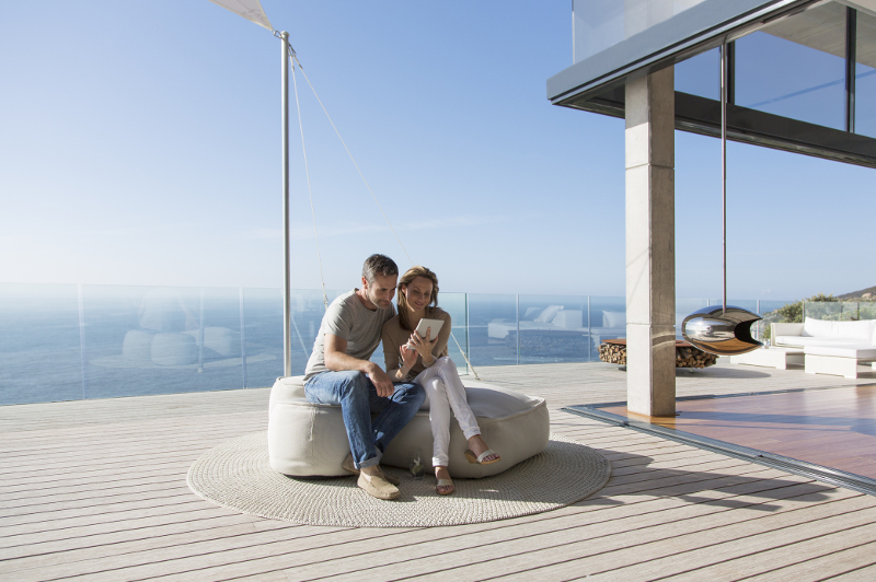 Couple on seaside deck look at tablet