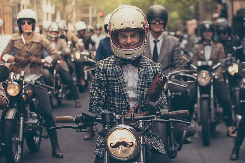 Men in old fashioned dress on motorbikes