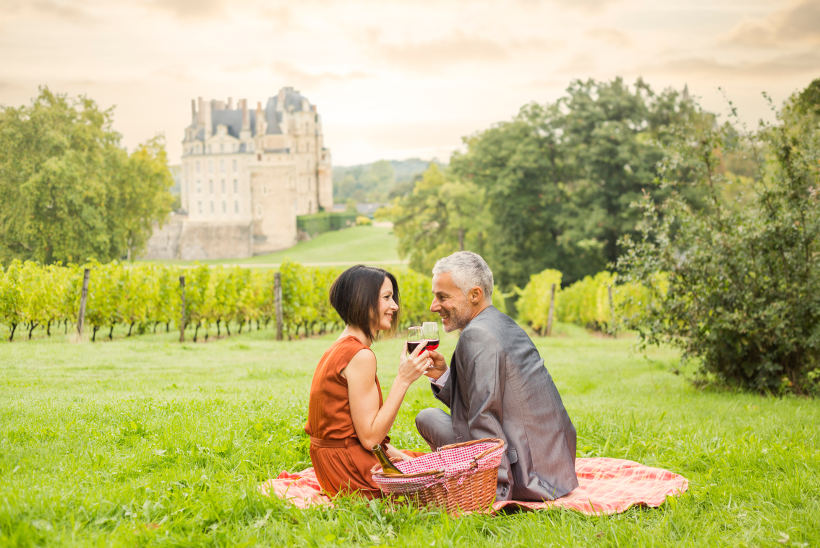 Travel Associates couple having picnic in french vineyard
