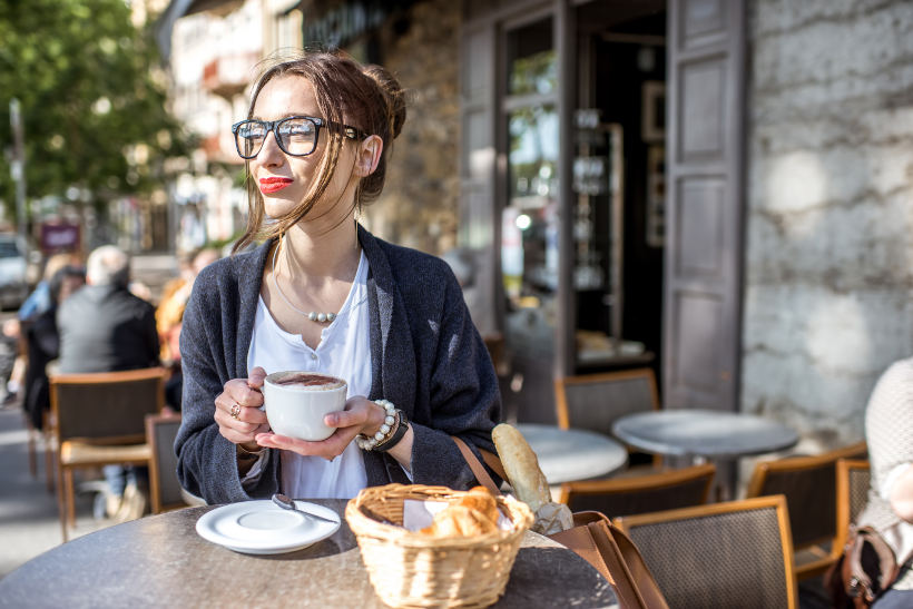 Travel Associates woman drinking coffee outside Lyon cafe