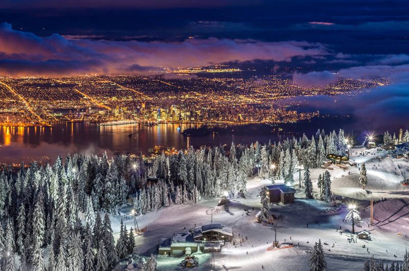 Snowy mountain top with view of Vancouver at night