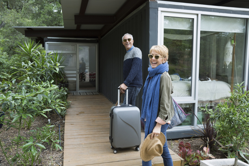 Couple arrive at vacation home with suitcases