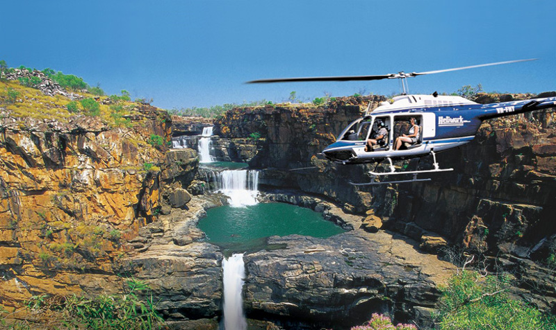 Helicopter flies over Mitchell Falls in the Kimberley