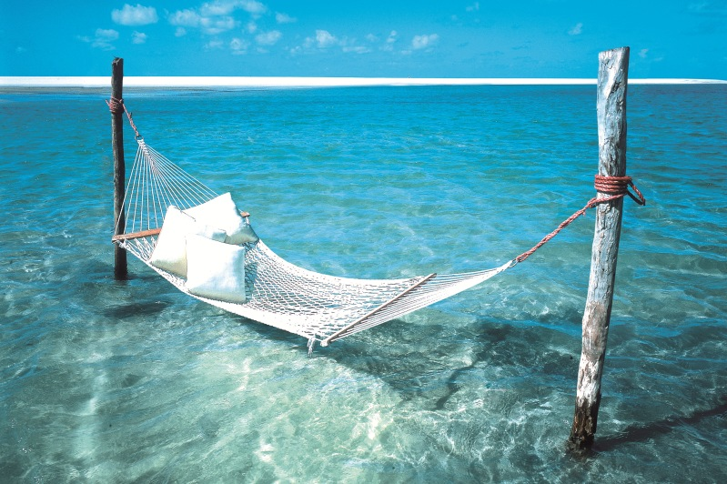 Hammock hangs over turquoise water