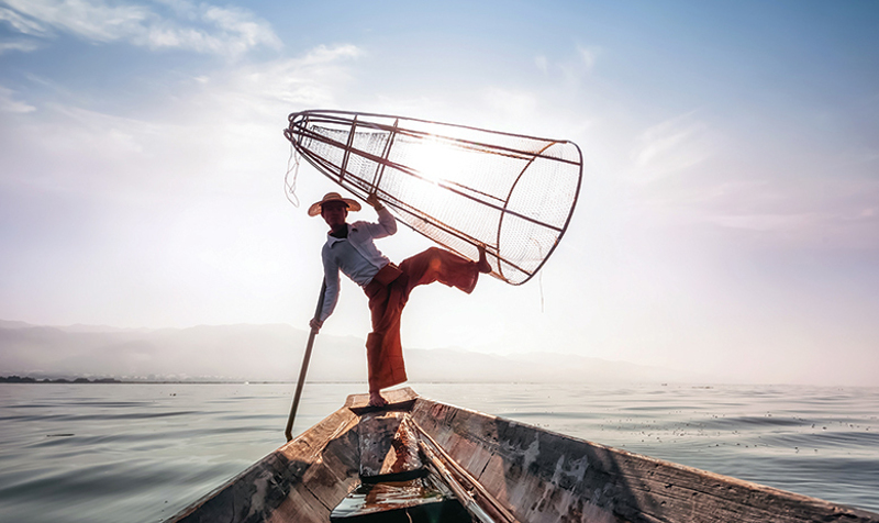 Burmese fisherman with next balanced on foot