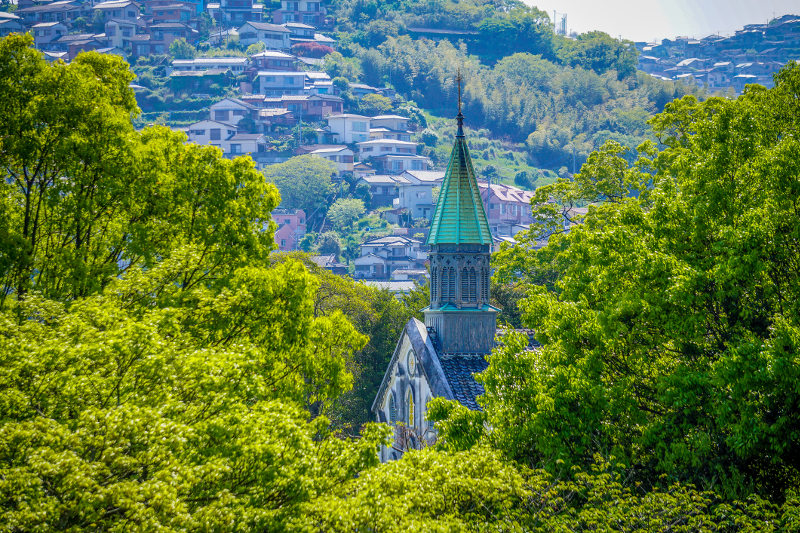 Spire of Oura Catholic church seen through green foliage of Nagasaki