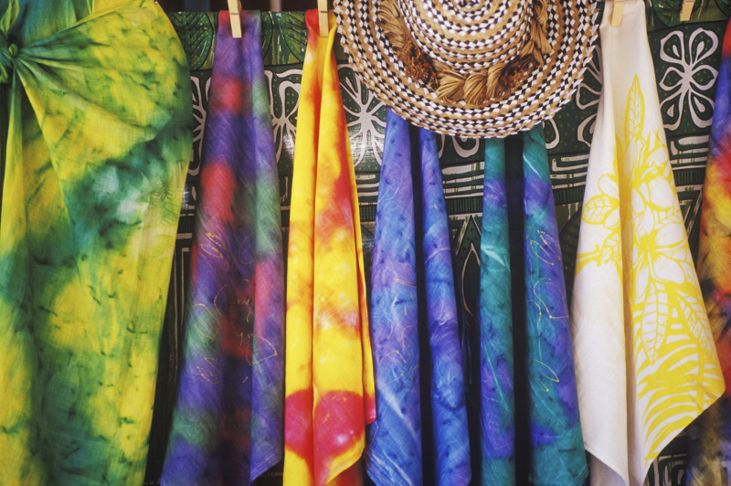Colourful sarongs and a woven hat at a market stall
