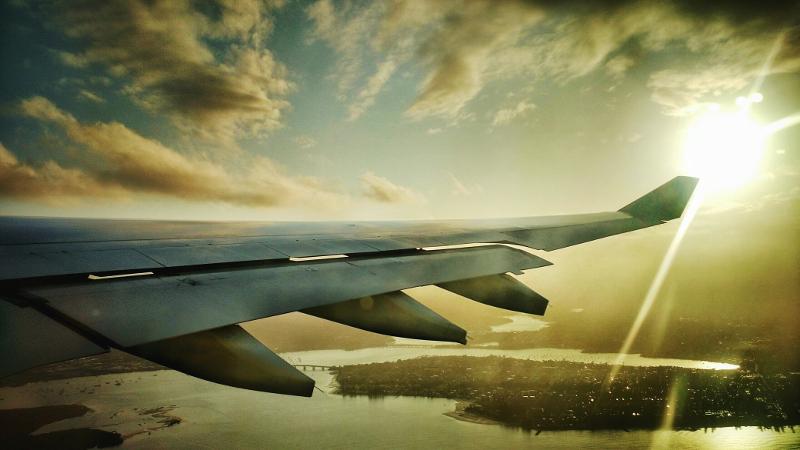 Plane flies over landscape in sunset