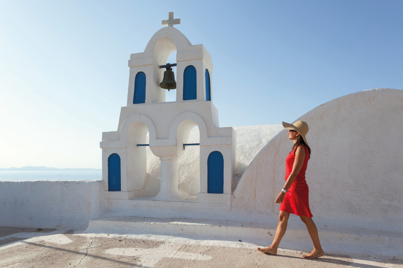 Woman in red dress walks through white Santorini buildings