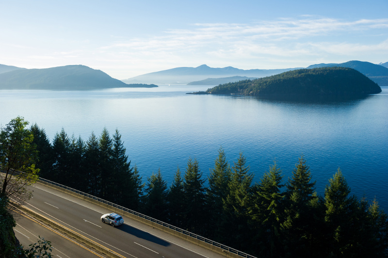 Aerial view of car driving on highway through fir trees on edge of blue lake