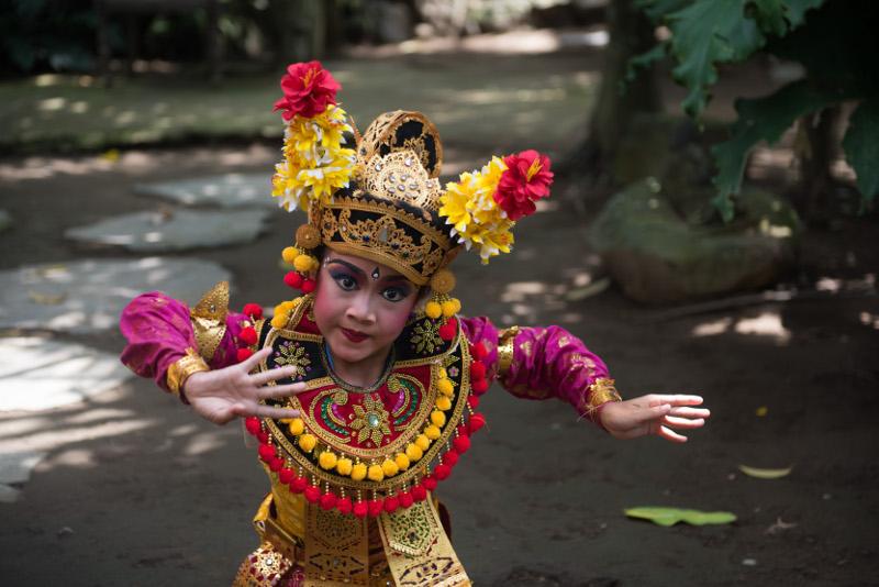 Balinese temple dancer poses in garden
