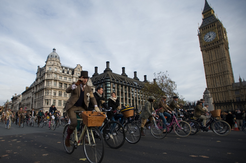 People in old fashioned costume cycle past Big Ben