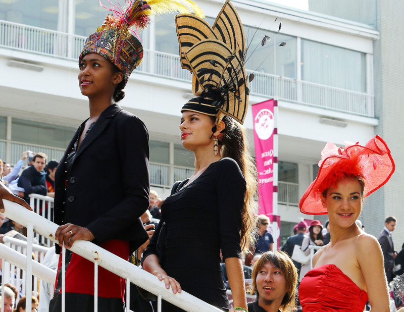 Elegant fashionistas in hats on race day
