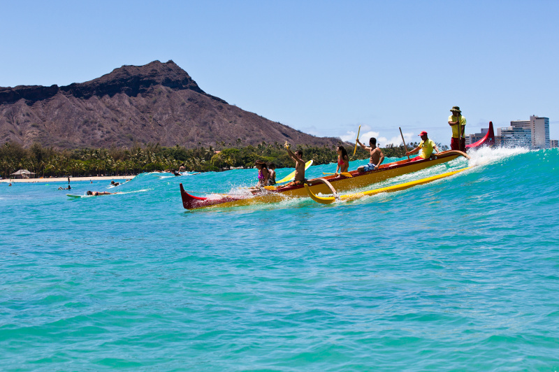 A group riding a wave in a canoe