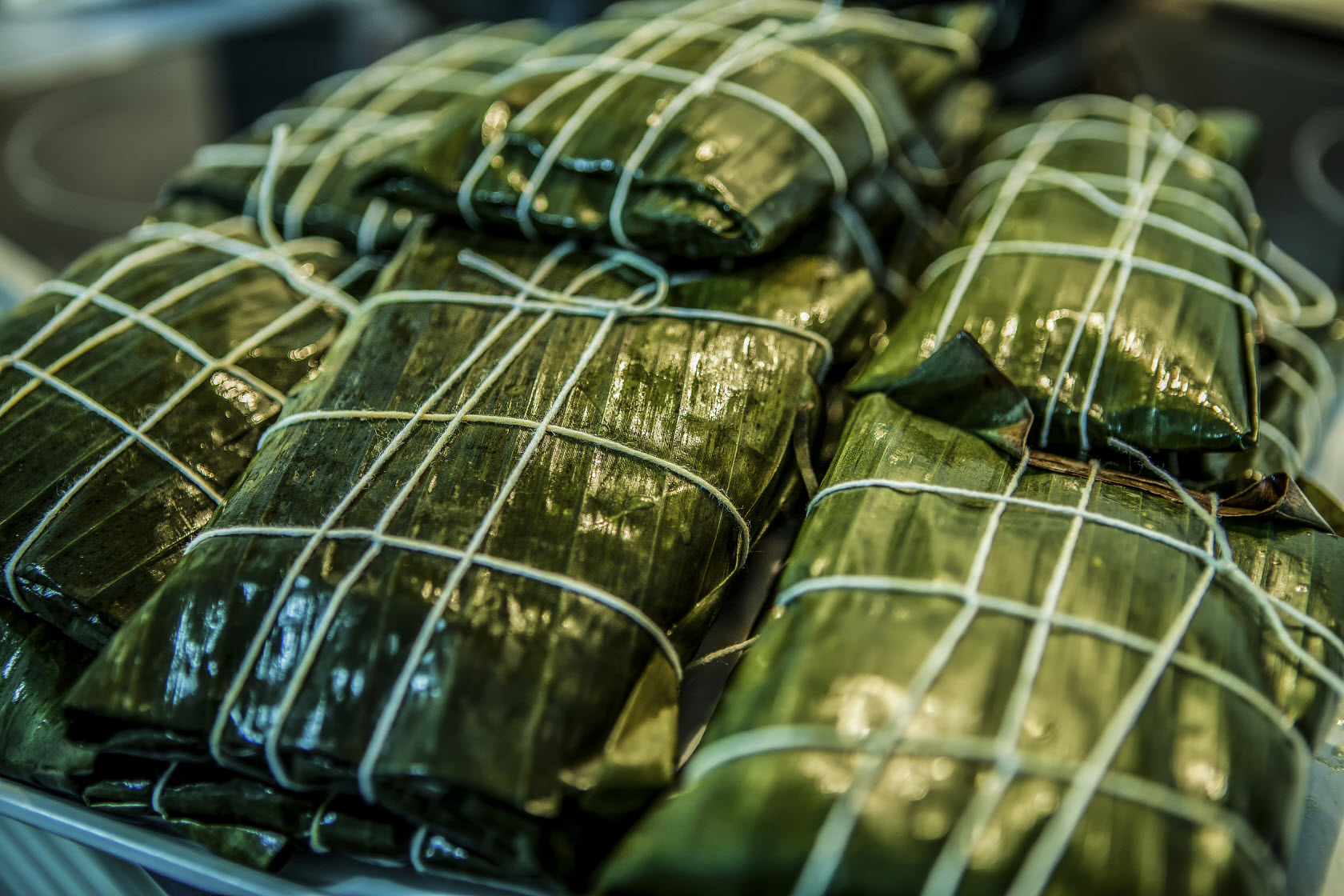 This image:  Ecuadorians wrap tamales wrapped in banana leaves, rather than corn leaves elsewhere in South America.