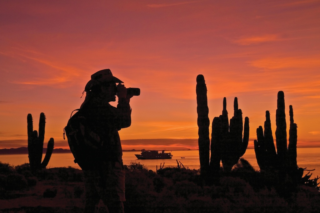 Photographer at sunrise on Isla San Esteban, Baja California with expedition ship Sea Lion in the background. Source:  Ralph Lee Hopkins