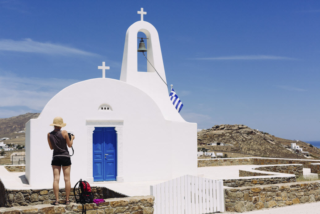 This image: Female traveller photographing traditional Greek church.