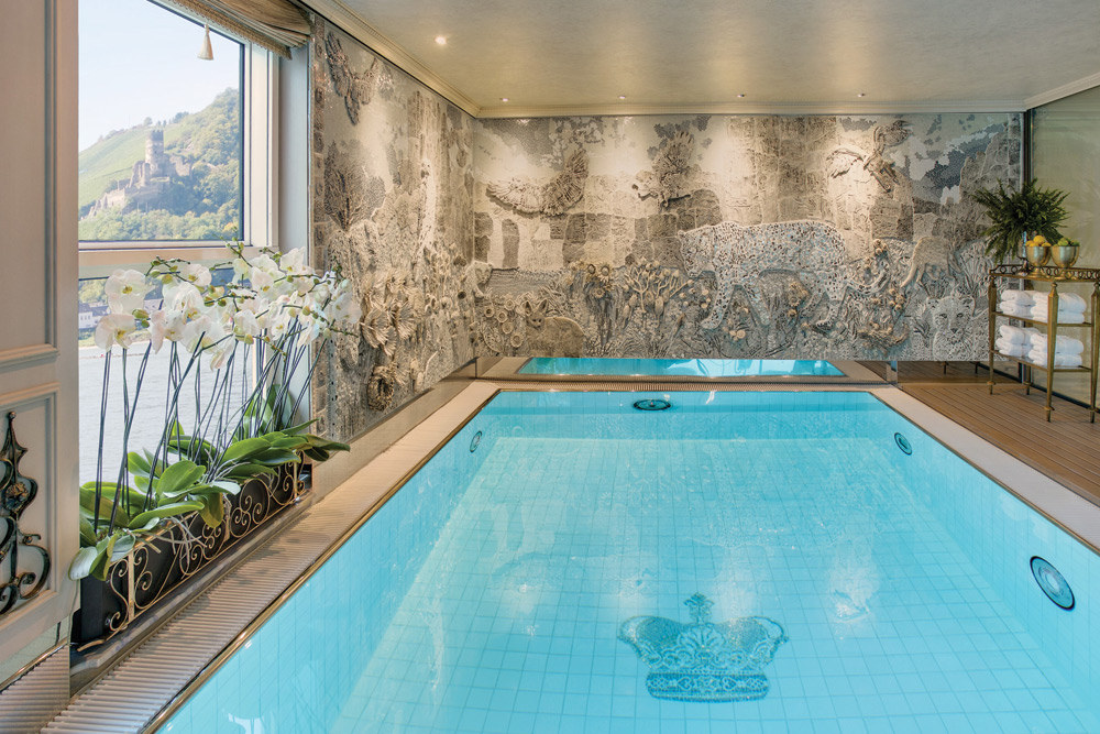 The heated indoor pools on Uniworld's Super Ships are enveloped by glass walls and mosaics, with poolside fitness classes daily. Image courtesy of Uniworld Boutique River Cruise Collection.