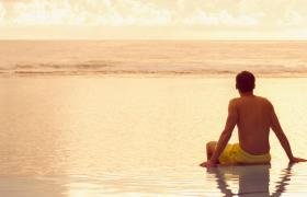Travel Associates man sitting on infinity pool at dusk rarotonga